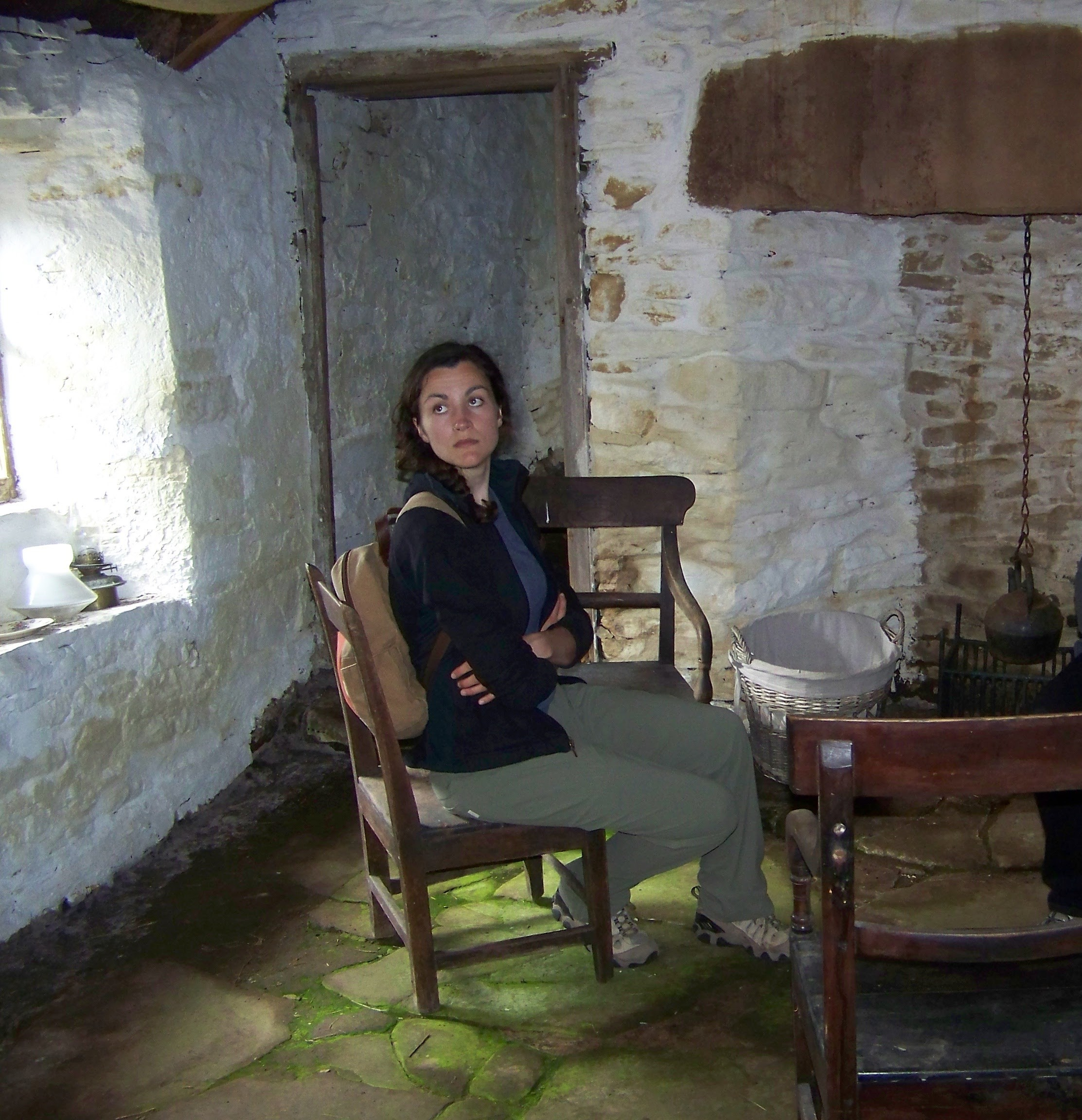 Woman sitting in an antique chair in the Craa's Nest croft museum, Hoy, Orkney