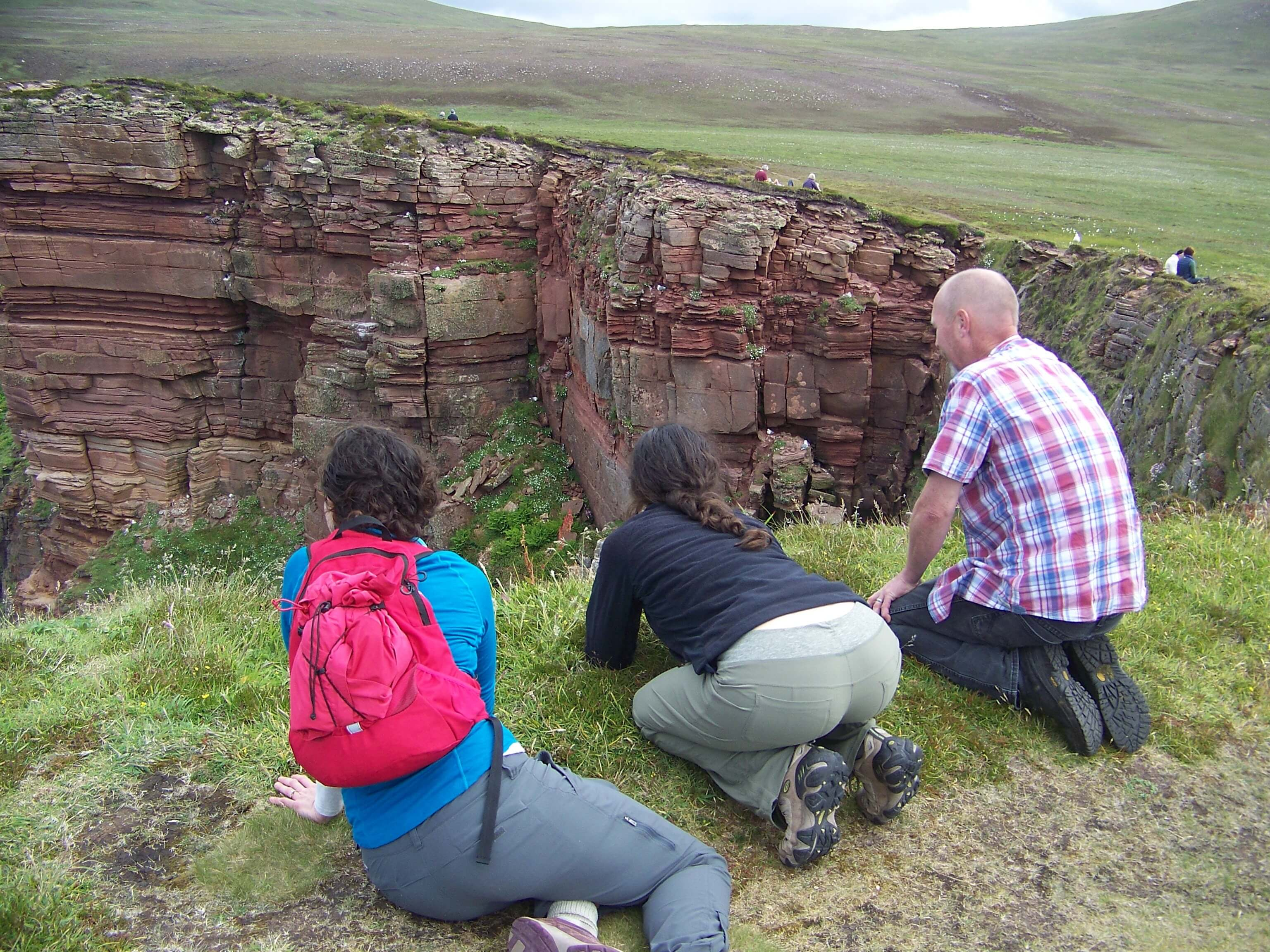 Hikers looking for puffins on Orkney cliffs.
