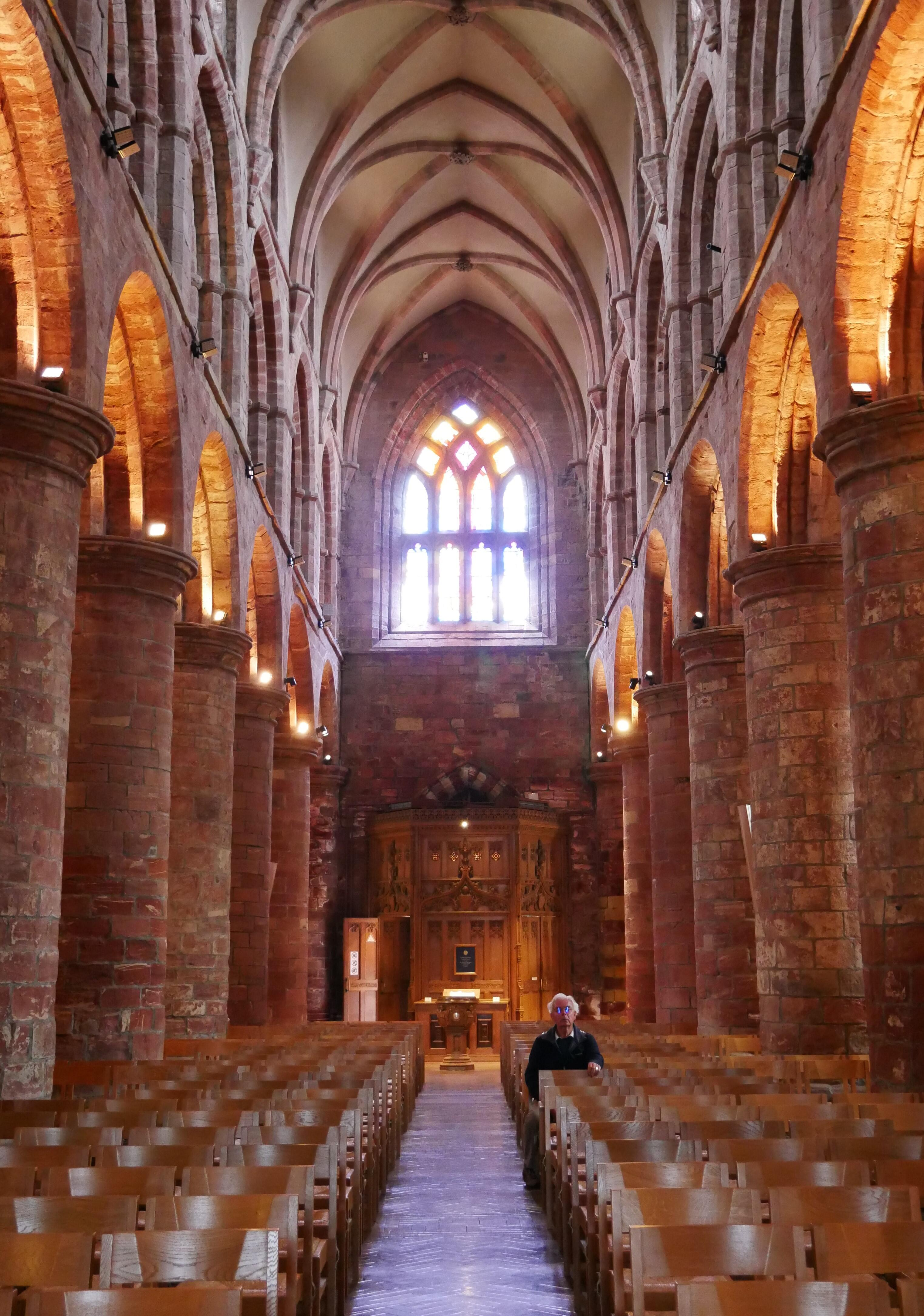 A man reflects quietly in Kirkwall's cathedral - Orkney Islands, Scotland, UK