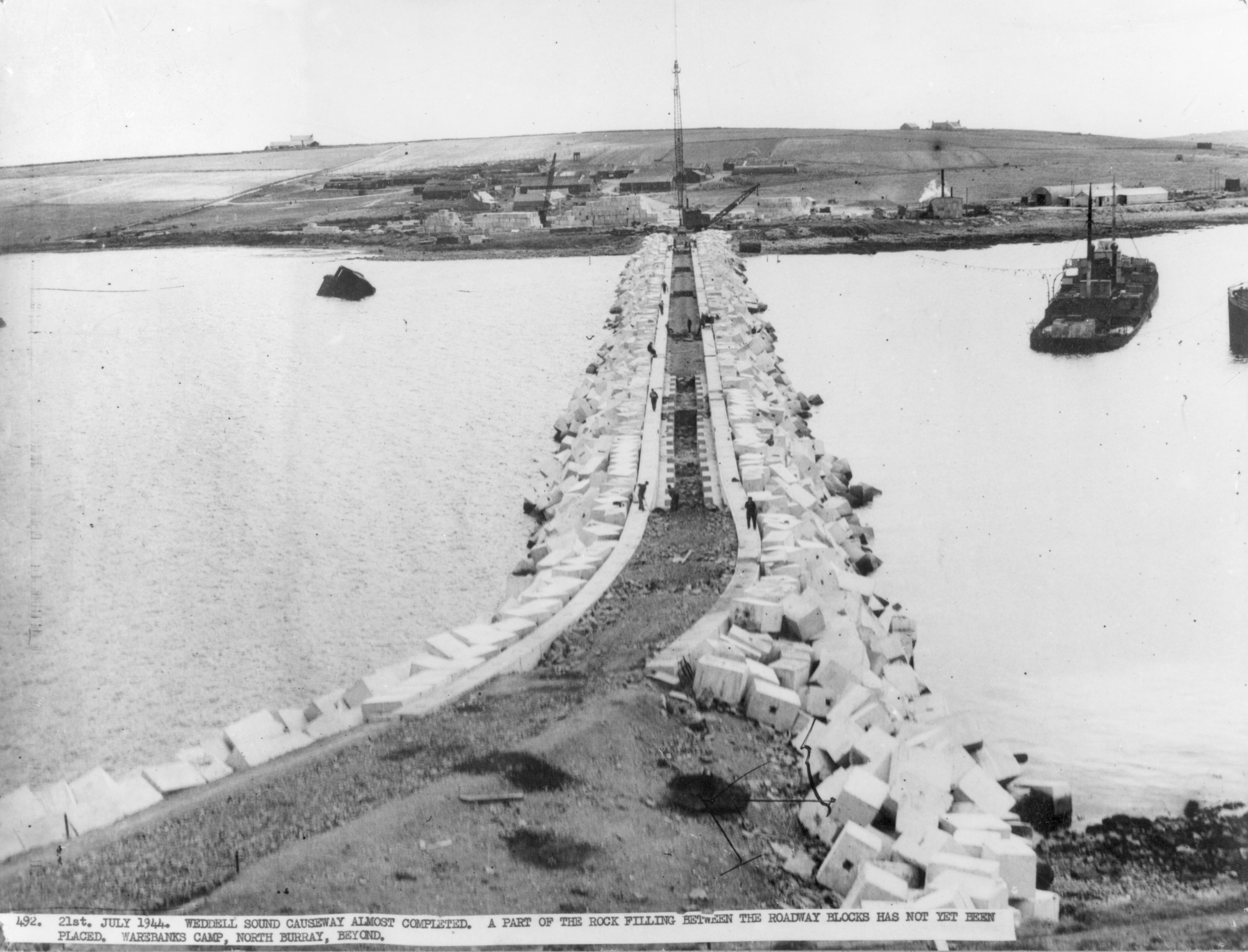 East Weddell Sound causeway, Churchill Barrier no. 3. A part of the rock fill between the blocks has not yet been placed. Camp 34, Burray, in the background, as seen from Glimps Holm.