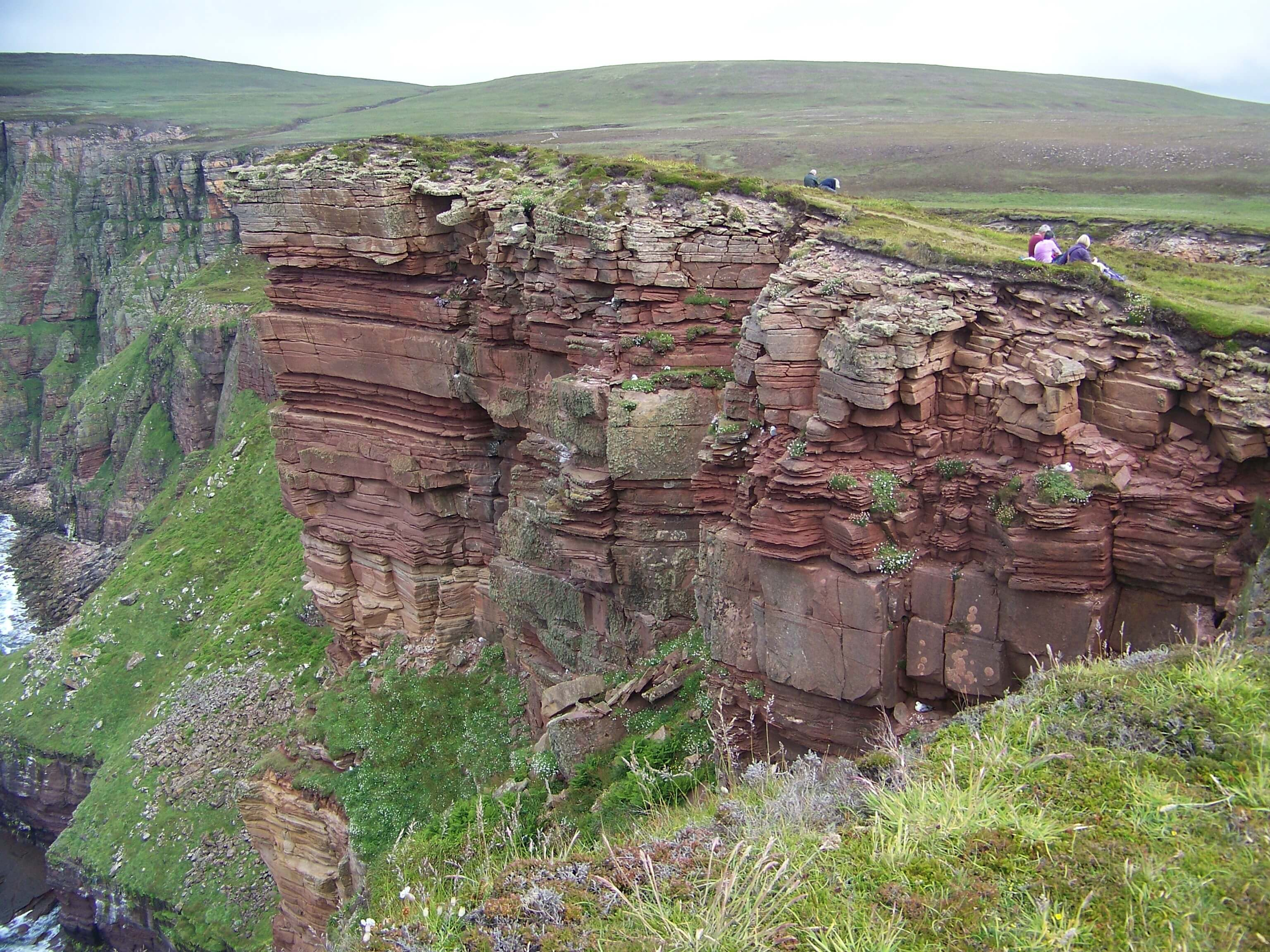 Hikers along red sandstone cliffs, Hoy, Orkney