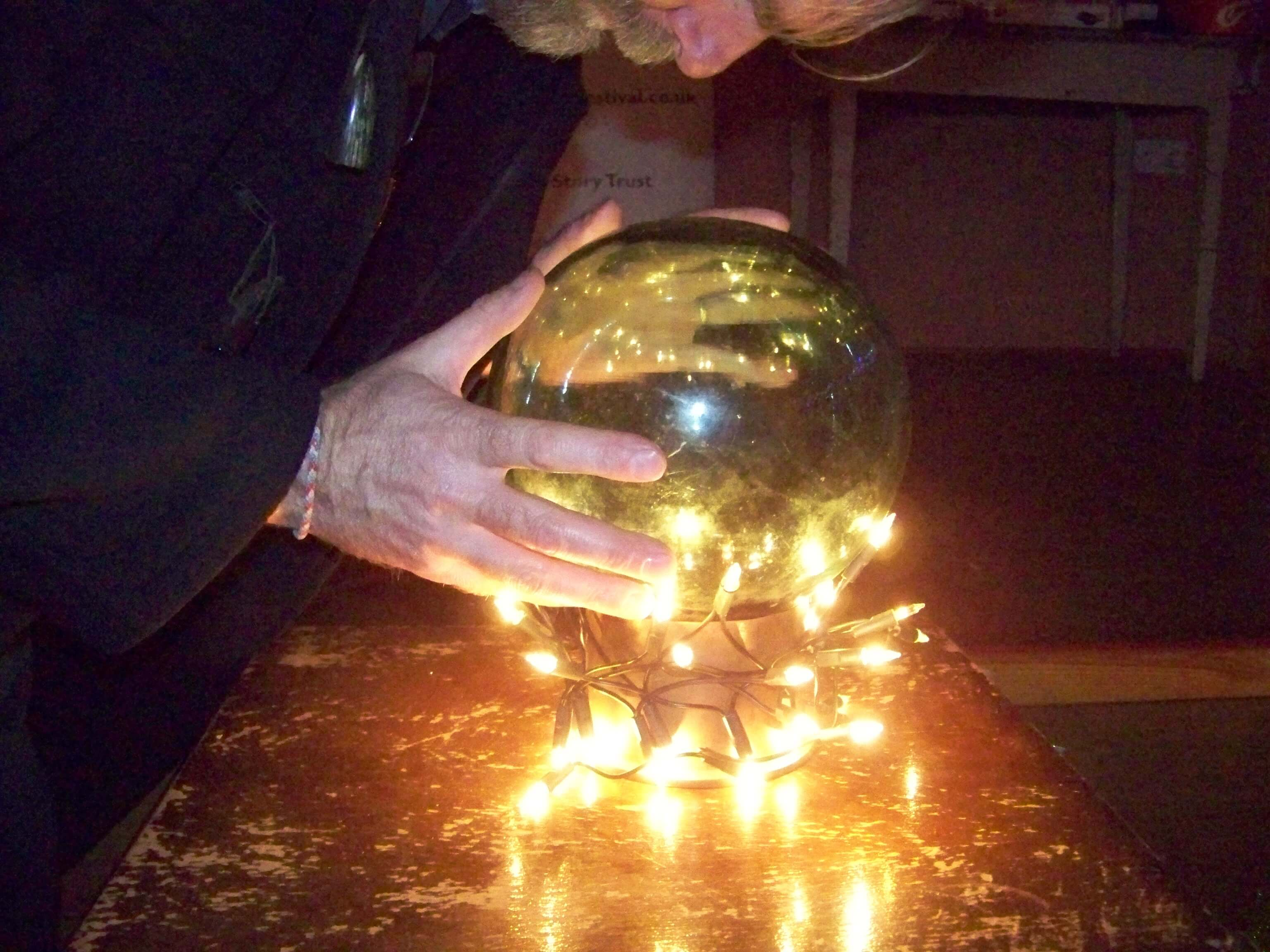 Andrew Hollinrake looks into his crystal ball at a storytelling event in Orkney, Scotland