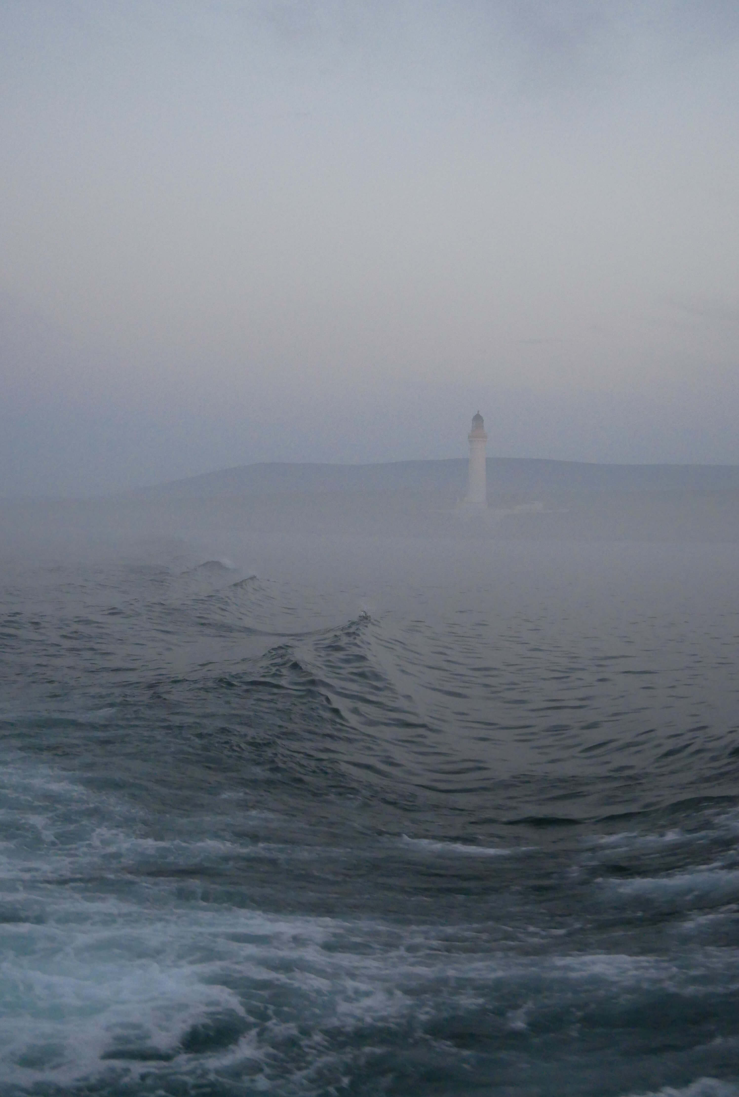 Hoy High lighthouse on the island of Graemsay, as seen from the ferry from Hoy to Stromness, Orkney Islands, Scotland.